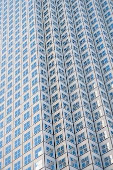 夜の現代の未来的なダウンタウンのガラスの高層ビルの超高層ビルのスチールブルーの背景へのパノラマと遠近法の広角ビュー成功した産業建築のビジネスコンセプト