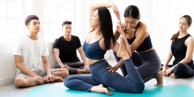 Панорамные азиатские люди изучают йогу в фитнес-клубе. инструктор тренирует и корректирует правильную позу