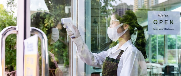 Panoramic asian waitress with face mask taking temperature to customer before getting in restaurant. new normal restaurant lifestyle concept after coronavirus covid-19 pandemic.