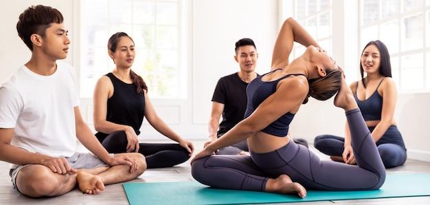 Panoramic asian yoga instructor coach do king pigeon pose in yoga studio