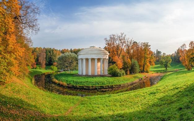 파블로프 스크 공원에는 우정의 사원이있는 파노라마 가을 풍경이 있습니다. 러시아 상트 페테르부르크
