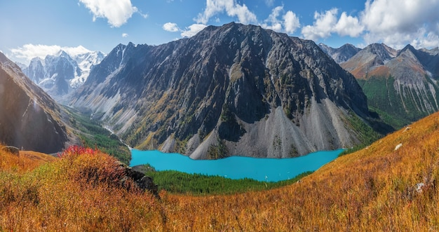 山々を背景に山の湖へのパノラマの秋の景色。高山の谷に湖のある雰囲気のある黄金の風景。アルタイ山脈の低いshavlinskoe湖。