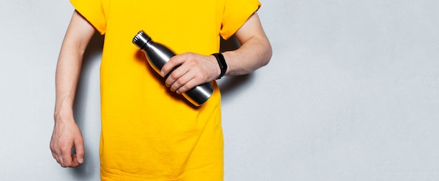 Panoramic banner view; close-up of male hands holding reusable steel thermo water bottle on textured  grey background with copy space. young man wearing yellow.
