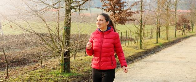 Панорамный вид молодой женщины, бегущей осенью осень