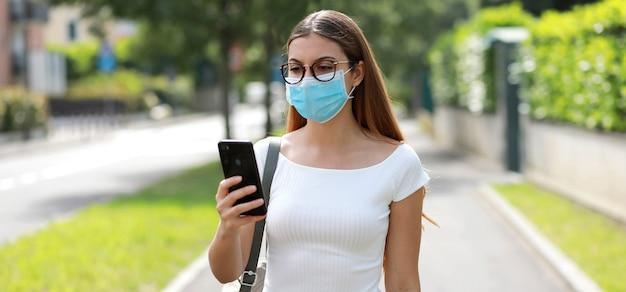街で携帯電話でメッセージングの医療マスクを持つ若い女性のパノラマバナービュー。