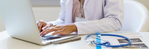 病院でラップトップコンピューターで作業している白い制服を着た女性医師とパノラマバナー