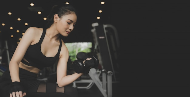 Panoramic banner. young pretty asian slim body woman in black sport bra exercise with dumbbell in fitness gym and dark background, bodybuilder, healthy lifestyle, workout and sport training concept