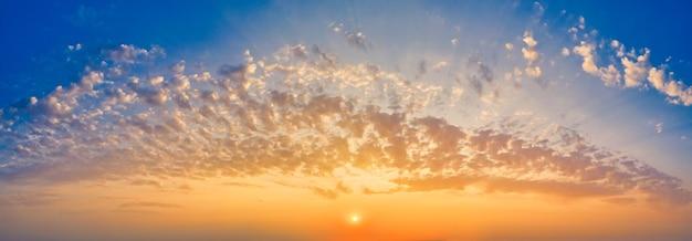 Панорамное голубое небо с желтым осенним солнцем и слоисто-кучевыми облаками