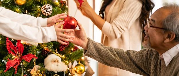 파노라마 가까이 손을 작은 아시아 소녀 할아버지와 크리스마스 트리를 장식합니다.