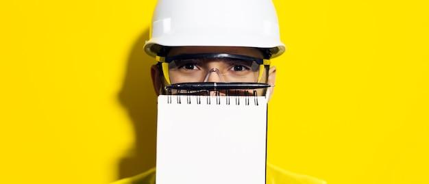 ノートブックの後ろに隠れている若いエンジニアの男のパノラマのクローズアップの肖像画