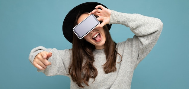Panoramic closeup of attractive young happy woman wearing black hat and grey sweater holding phone pointing finger finger at camera isolated on background.mock up, cutout, empty space