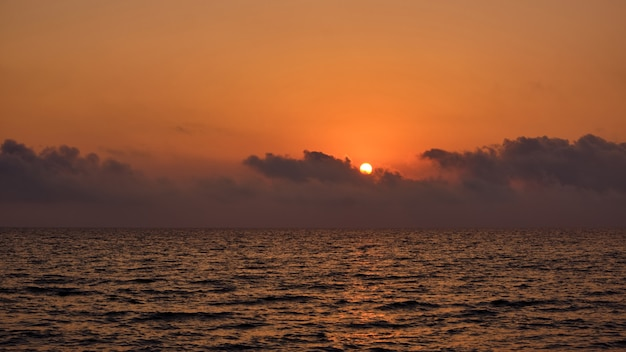 Panoramic dramatic sunrise with sun round, sky with clouds and sea at dusk