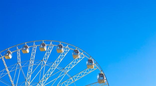 푸른 하늘을 배경으로 회전하는 캐빈이 있는 탁 트인 관람차 회전목마는 공간을 복사합니다. 놀이 공원에서 여름 재미입니다.