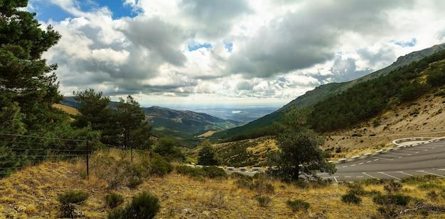 画像の背景に谷と湖のパノラマの緑の山の風景。