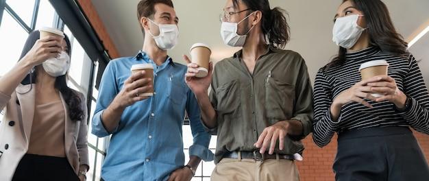 昼休みの後にオフィスに戻ってテイクアウトのコーヒーカップを持つビジネスワーカーチームのパノラマグループ。彼らは、コロナウイルスcovid-19の拡散を防ぐ新しい通常のオフィスで防護マスクを着用します。