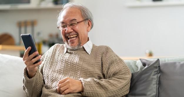 パノラマの幸せな退職老人リビングルームのソファに座って携帯電話を使用