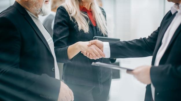 Деловые партнеры панорамного изображения пожимают друг другу руки во время переговоров