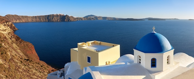 Panoramic image of local church with blue cupola in oia on santorini island