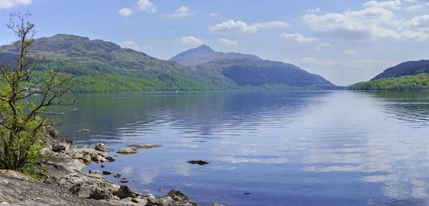 ローモンド湖の西岸にある反射のある集落、インバーアグラスの美しい風景のパノラマ画像、アーガイルアンドビュート、スコットランド