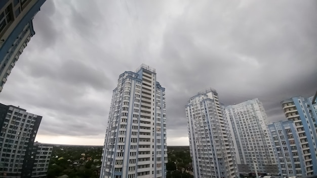 Панорамное изображение темного неба, покрытого серыми и черными дождевыми облаками над высоким жилым зданием в городе. городской пейзаж перед бурей