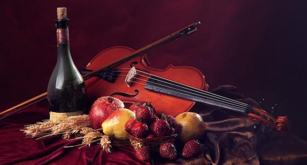 パノラマ画像古いワインとウェットフルーツのボトルの横にあるクラレットに弓を持ったバイオリン。
