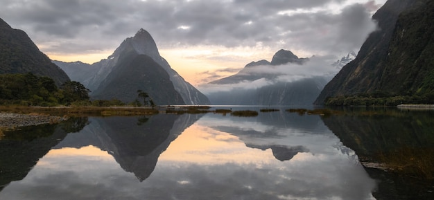 Panoramic landscape shot of sunrise in fjord with peaks shrouded in cloudsmilford soundnew zealand