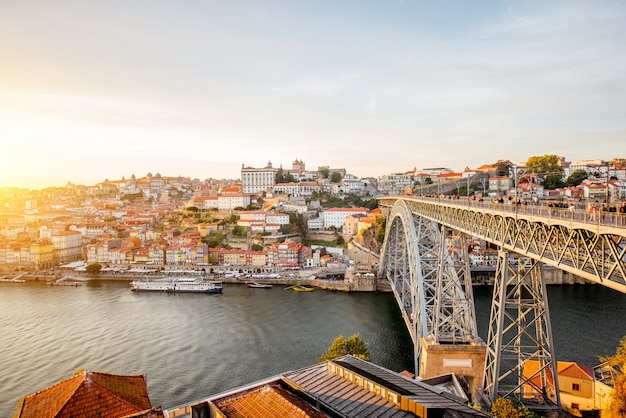 Панорамный пейзажный вид на старый город с рекой дору и знаменитый железный мост в городе порту во время заката в португалии