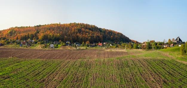 丘と村を背景にした農地のパノラマ風景。