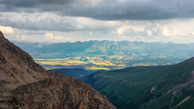 日光の下で雑多な山の谷のパノラマの山の風景。多色の谷の素晴らしい日当たりの良い高原の風景。珍しいファンタジーの風景。