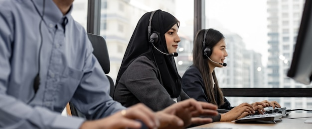 Panoramic of muslim woman and group of diverse telemarketing customer service staff team in call center. call center worker accompanied by team. smiling of customer support operator at work.