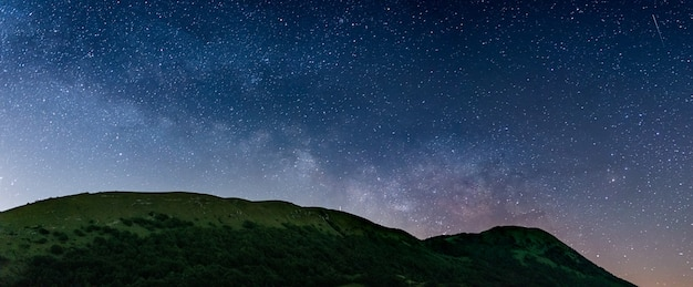 Panoramic night sky over montelago highlands, marche, italy