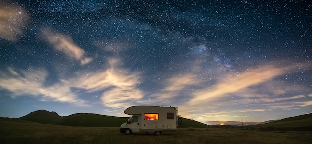 Панорамное ночное небо над нагорьем кампо-императоре, абруццо, италия. арка галактики млечный путь и звезды над освещенным автофургоном. свобода кемпинга в уникальном ландшафте холмов.