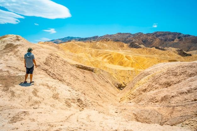 Панорамный снимок молодого человека, наслаждающегося видом на смотровую площадку забриски-пойнт, калифорния. соединенные штаты