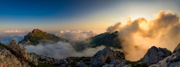 Панорамный вид на горы с красными облаками заходящего солнца