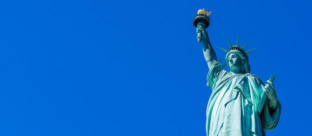 Панорамный статуя свободы в нью-йорке. статуя свободы с голубым небом над гудзоном на острове. достопримечательности нижнего манхэттена нью-йорк.