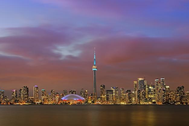 Панорамный освещенный городской пейзаж центра торонто над озером онтарио в сумерках, торонто, канада