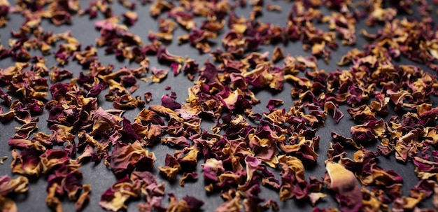 Panoramic photo of dried tea rose leaves, on the black table. pattern idea.
