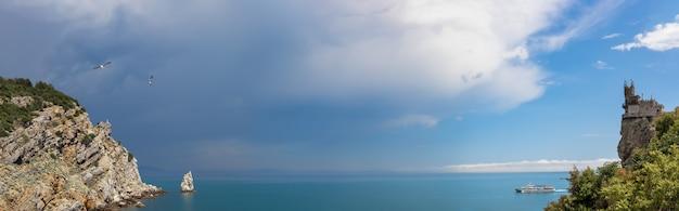 ツバメの巣の城の隣の岩の多い海岸の劇的な空のパノラマ写真