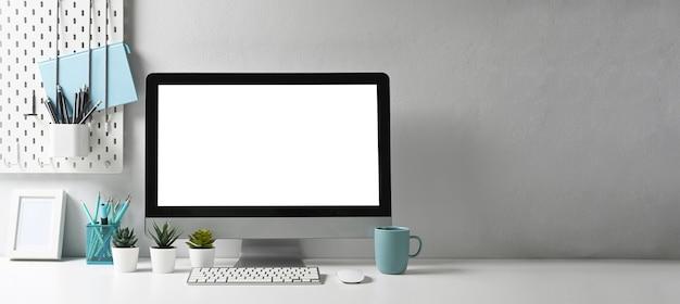 컴퓨터 및 사무용품 가제트를 모의하는 세련된 작업 공간의 파노라마 사진. 그래픽 디스플레이 몽타주에 대한 빈 화면 및 복사 공간.