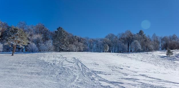 Панорамное фото зимнего пейзажа со снежным спуском для катания на санках, тюбингах и снегоходах ранним утром