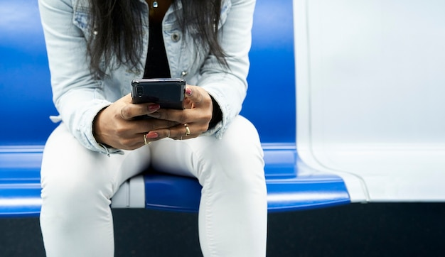 Panoramic photograph of the hands of an unrecognizable woman sitting in the subway car using a smartphone.