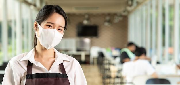 パノラマポートレート魅力的なアジアのウェイトレスはフェイスマスクを着用します。新しい通常のレストランのライフスタイルコンセプト。