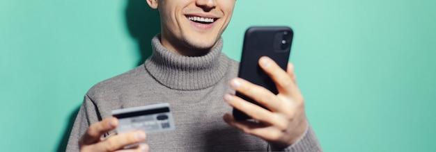 Панорамный портрет улыбающегося парня, держащего смартфон и кредитную банковскую карту на голубом