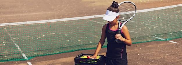 テニスコートでテニスをしている10代の少女のパノラマの肖像画。肩にラケットを持って、別のバルを取ります。特別なスポーツユニフォームを着ています。