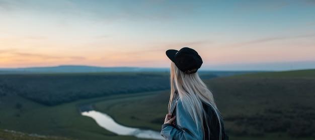 Панорамный портрет молодой блондинки на пике холмов на закате.