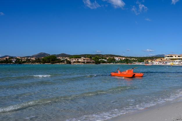 Панорамный вид на море и пляж на фоне гор гольфо аранчи, сардиния. на переднем плане катамаран спасатели