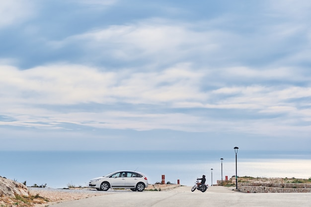 Panoramic sea view with a car and bike on foreground