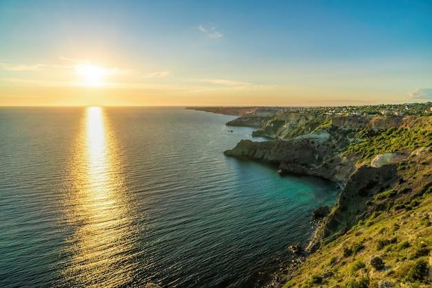 Панорамный морской пейзаж, вид на скалистый берег моря, спокойное лазурное море и яркий закат.