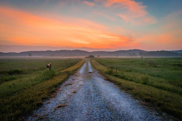 Ripresa panoramica di un sentiero sterrato in mezzo a un campo con la sagoma delle montagne al tramonto