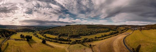 Scatto panoramico di campi agricoli sotto la luce del sole e un cielo nuvoloso in campagna